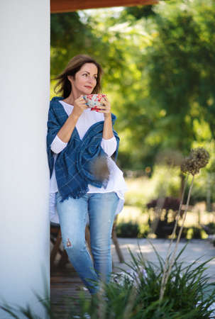 Mature woman with cup of tea resting outdoors in backyard.