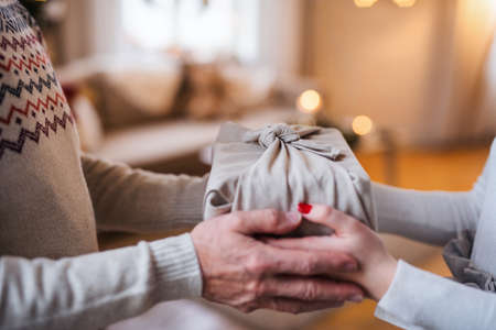Unrecognizabe woman giving present to senior man indoors at home at Christmas. Standard-Bild