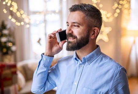 Mature man indoors at home at Christmas, using smartphone.