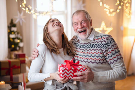 Senior man with young woman indoors at home at Christmas, holding present. Standard-Bild