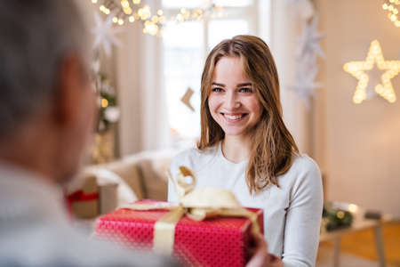 Young woman giving present to unrecognizable grandfather indoors at home at Christmas.