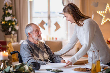 Young woman with senior grandfather in wheelchair indoors at home at Christmas.