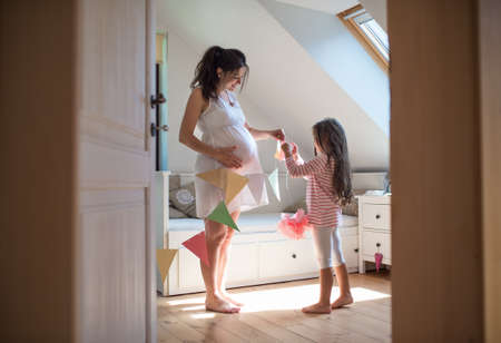 Portrait of pregnant woman with small daughter indoors at home, decorating bedroom. Standard-Bild