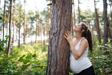 Portrait of happy pregnant woman outdoors in nature, tree hugging concept.