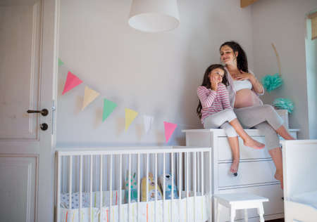Portrait of pregnant woman with small daughter indoors at home, sitting on chest of drawers.