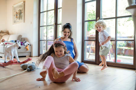 Pregnant woman with small children indoors at home, playing.