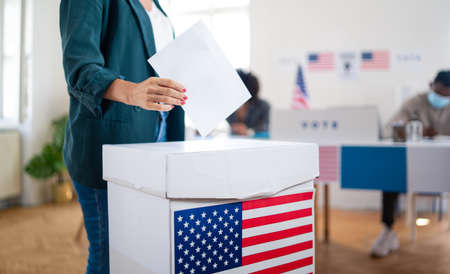 Unrecognizable woman putting her vote in the ballot box, usa and coronavirus elections. Standard-Bild