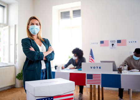 Young woman putting her vote in the ballot box, usa elections and coronavirus.