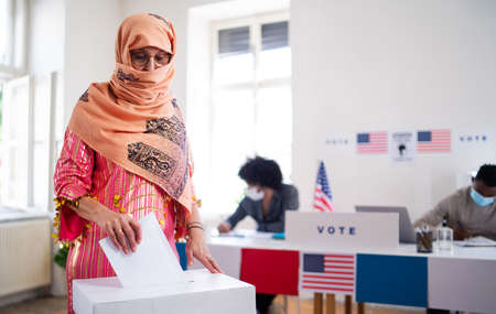 Islamic woman voter putting her vote in the ballot box, usa elections and coronavirus.