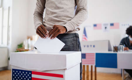 Unrecognizable african-american man putting his vote in the ballot box, usa elections and coronavirus. Standard-Bild