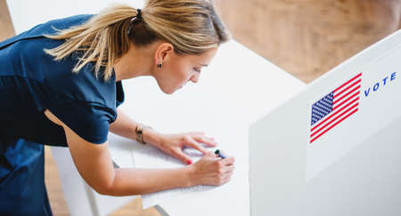 Top view portrait of woman voter in polling place, usa elections concept. Standard-Bild