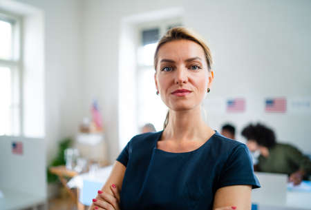 Portrait of confident woman voter in polling place, usa elections concept. Standard-Bild