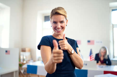 Portrait of happy woman voter with tumb up in polling place, usa elections concept.