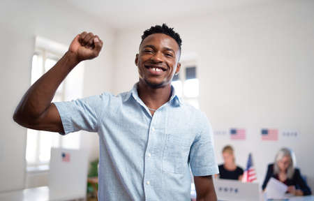 Happy african-american man voter looking at camera in the polling place, usa elections.