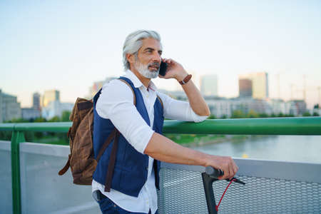 Portrait of mature man with electric scooter outdoors in city, using smartphone. Imagens