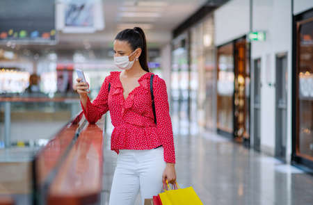 Woman with face mask standing with smartphone indoors in shopping center, coronavirus concept. Stockfoto