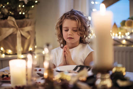 Small girl sitting at the table indoors at Christmas, praying.