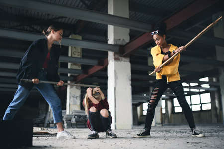 Teenage girl attacked by thugs in abandoned building, gang violence and bullying concept. Banque d'images