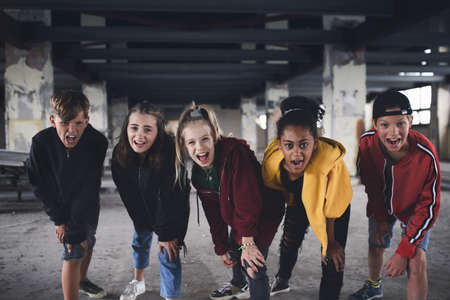 Group of teenagers gang standing indoors in abandoned building, looking at camera.