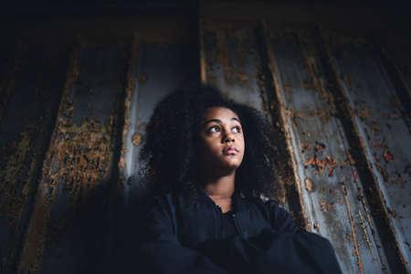 Portrait of mixed-race teenager girl standing indoors in abandoned building. Banco de Imagens