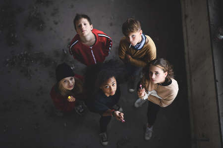 Top view of group of teenagers gang standing indoors in abandoned building, looking at camera.