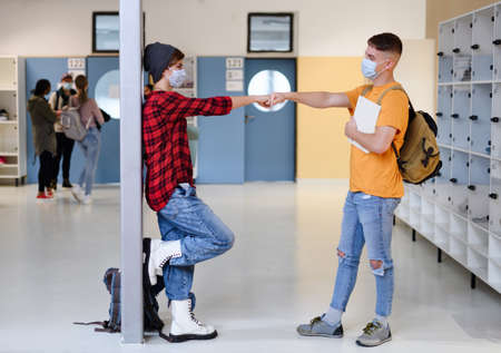 Young students friends with face masks back at college or university, coronavirus concept.
