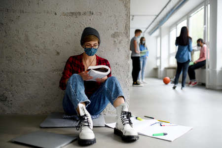 Young student with face mask sitting on floor back at college or university, coronavirus concept. Reklamní fotografie