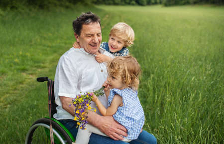 Small children with senior grandfather in wheelchair on a walk on meadow in nature. Banco de Imagens