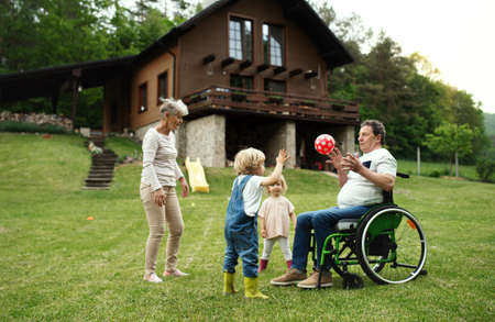 Small children with senior grandparents in wheelchair playing with a ball in garden.