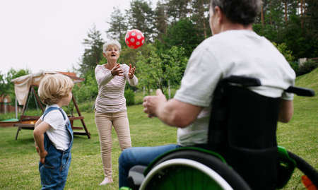 Small boy with senior grandparents in wheelchair playing with a ball in garden.
