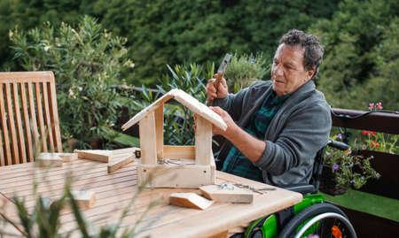 Senior man in wheelchair constructing birdhouse outdoors on terrace, diy project.