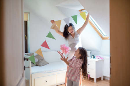 Portrait of pregnant woman with small daughter indoors at home, decorating bedroom. Archivio Fotografico