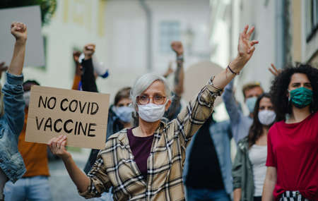 People with placards and posters on public demonstration, no covid vaccine and coronavirus concept.