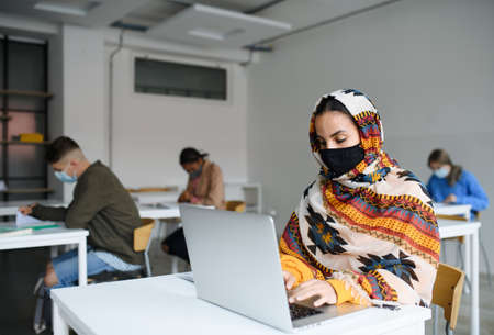 Islamic student with face mask at desks at college or university, coronavirus concept.