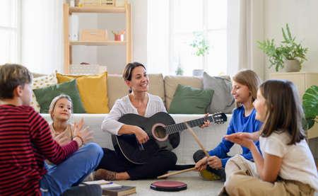 Group of homeschooling children with teacher having music lesson indoors, coronavirus concept.