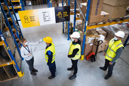Group of workers with face mask in warehouse, coronavirus and temperature measuring concept.