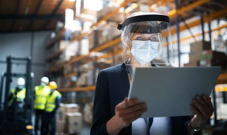 Manager with protective shield using tablet indoors in warehouse, coronavirus concept.