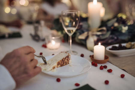 Unrecognizable man indoors at the table at Christmas dinner, eating cake. Stockfoto