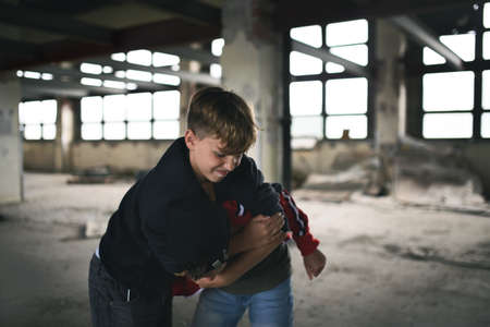 Teenage boy attacked by thug in abandoned building, gang violence and bullying concept. 版權商用圖片