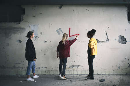Rear view of group of teenagers girl gang indoors in abandoned building, using spray paint on wall.