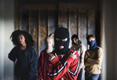Boy with mask with teenagers gang indoors in abandoned building, showing finger gun gesture. 版權商用圖片