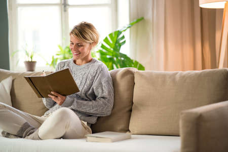 Portrait of woman relaxing indoors at home, mental health care concept.