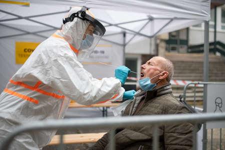 Senior man in covid-19 testing center outdoors on street, coronavirus and taking swab concept. Stock Photo