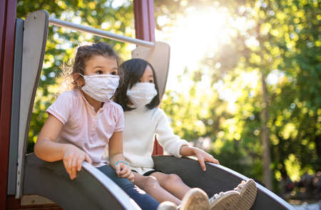Small girls with face mask on slide outdoors in town, coronavirus concept.