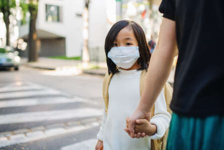 Portrait of small Japanese girl with mother walking outdoors in town, coronavirus concept.