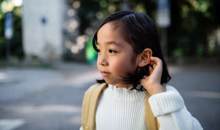 Portrait of small Japanese girl with backpack walking outdoors in town.