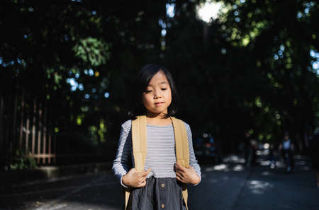 Portrait of small Japanese girl with backpack standing outdoors in town.
