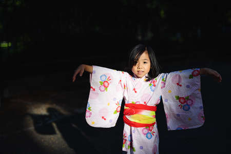 Portrait of small Japanese girl wearing kimono outdoors in town.