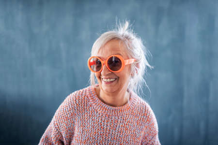 Portrait of senior woman with sunglasses standing indoors against dark background, laughing.
