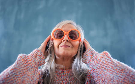 Portrait of senior woman with sunglasses standing indoors against dark background, listening to music.